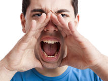 Shouting loud. Portrait of a young man shouting loud with hands on the mouth, isolated on white background Stock Images