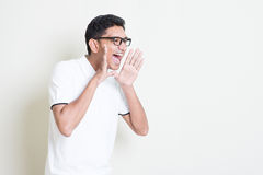 Shouting loud. Portrait of Indian guy shouting loud, mouth open and hand cupped beside. Asian man standing on plain background with shadow and copy space Royalty Free Stock Photography