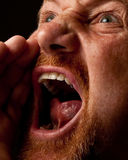 Shouting Loudly. Man with goatee shouting out loud with his hand raised to his mouth Stock Photo