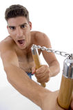 Shouting man holding nunchaku Stock Photography