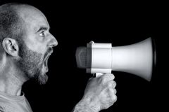 Shouting into megaphone. Man shouting into megaphone black background stock image