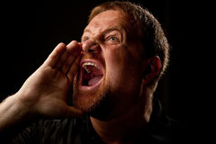 Shouting Out Loud. Man with goatee shouting out loud with his hand raised to his mouth Stock Photography