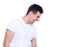 Shouting out loud. Side view of furious young man shouting and keeping eyes closed while standing isolated on white Stock Images