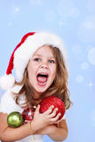 Shouting preschool girl in Santa hat. Portrait of a shouting girl in Santa hat holding Christmas decoration in hands Stock Images