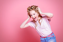 Shouting pretty girl. Portrait of a shouting pretty girl teenager with curlers in her blonde hair. Teen style, fashionable teen girl. Studio shot over pink Stock Photo