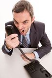 Shouting into receiver. Image of aggressive boss yelling into telephone receiver over white background Stock Photo