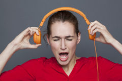 Shouting 20s girl for tinnitus headphones concept. Tinnitus headphones concept - shouting 20s girl listening to loud music with earphones on,removing her royalty free stock photos