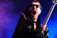 Shouting singer. Heavy metal musician  is playing electrical guitar. Shot in a studio Royalty Free Stock Photography