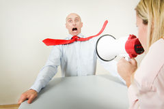 Shouting at stressed worker. A bullied male worker being blasted by the volume of his boss's shouting on a megaphone Stock Image