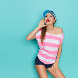 Shouting Summer Girl. Beautiful young woman in striped pink shirt and blue plastic cap holding hand on chin and shouting. Three quarter length studio shot on Stock Photography