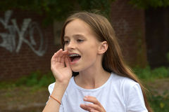 Shouting teenage girl. Teenager girl shouting with her hand at her mouth Royalty Free Stock Photos