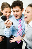 Shouting in telephone receiver. Closeup of three business people screaming into the phone receiver during their work Royalty Free Stock Photos