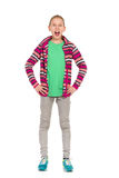 Shouting Ten Years Old Girl. Teen girl in striped fleece jacket, jeans and sneakers standing with hands on hip, looking at camera and shouting. Full length Royalty Free Stock Photos