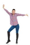 Shouting Young Woman With Arms Outstretched. Young woman in jeans, black boots and lumberjack shirt standing with arms outstretched and shouting. Full length Stock Image