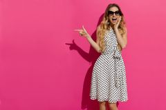 Shouting Young Woman Is Pointing At Pink Copy Space Stock Photo
