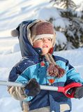 Shovel. Baby playing with shovel on snow Royalty Free Stock Images