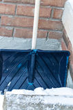 Shovel. A blue snow shovel leaning against a wall Royalty Free Stock Photos