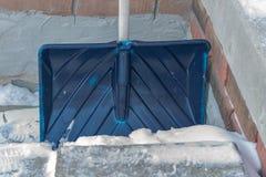 Shovel. A blue snow shovel leaning against a wall Stock Photos
