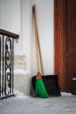Shovel and broom standing in the corner of the building on the street Stock Images