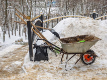 Shovel, broom, and a wheelbarrow of sand to clean snow. From the tracks in the park Stock Photo