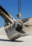 Shovel bucket. On a background of of blue sky and of rubble Royalty Free Stock Photo