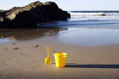 Shovel and bucket on beach. Yellow shovel and bucket sitting on an empty beach near the ocean royalty free stock photography
