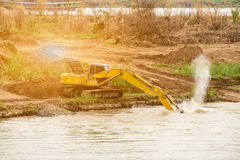 Shovel bucket on river bank , lift loads, construction machinery Royalty Free Stock Photos