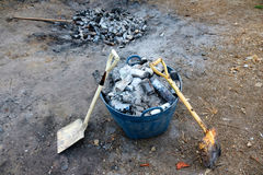 Shovel and burned cans and glass bottles. Stock Photos