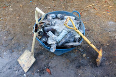 Shovel and burned cans and glass bottles. Royalty Free Stock Photo