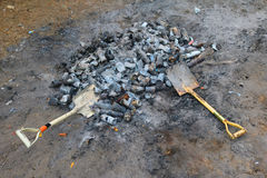 Shovel and burned cans and glass bottles. Stock Images