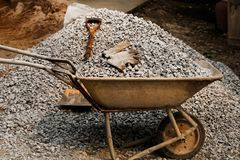 Shovel with cement cart and gravel black rock on construction site for background. Construction starts with planning, design, and. Financing it continues until stock photo