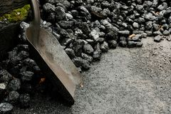 Shovel and coal at railway station. A shovel stands beside a pile of black coal at a railway station coal shed royalty free stock image