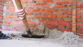 Shovel digging sand. Hands holding shovel dig sand near red brick wall. Construction concept.  stock video