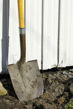Shovel in earth against garden shed Stock Photos