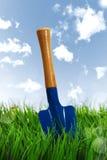 Shovel on grass over sky Stock Images