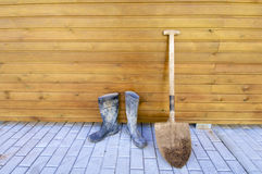 Shovel and gumboots. Based on a wooden wall Royalty Free Stock Photography