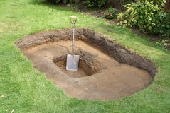 Shovel in hole for pond. A hole dug in a garden lawn in preparation for making a pond Stock Photos