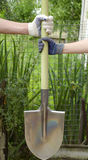 Shovel. Male and female hands in gloves holding a shovel in the background of the garden Royalty Free Stock Photography