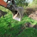The shovel of a mini digger in the meadow while working in summer. Backhoe shovel in the garden at work stock photography