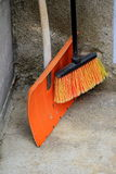Shovel and an orange broom Stock Photo