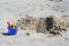 Shovel, pail and sand pit. A Shovel, pail and sand pit on the beach stock image