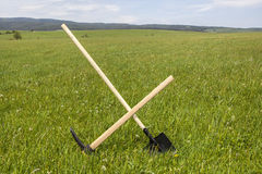 Shovel and Pickaxe Stuck in the Ground Royalty Free Stock Images