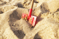 Shovel placed in the sand. Red colored shovel which has been placed into sand. The shot was taken during the golden hour giving the image a golden feel to it royalty free stock image