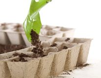 Shovel Placing Soil into Eco-friendly Compost Pots. Hands using a green shovel to place soil from a silver pail into eco-friendly Composted Cow Manure Pots used Royalty Free Stock Photography