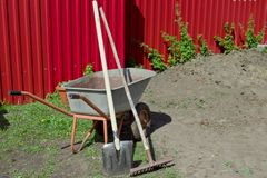 Shovel, rake and wheelbarrow against the red fence. Agricultural works Stock Photos
