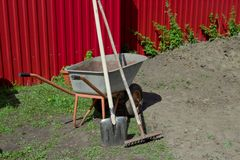 Shovel, rake and wheelbarrow against the red fence. Agricultural works Royalty Free Stock Image