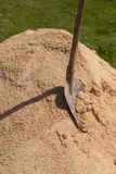 A shovel in a sand. Shovel in a pile of sand at a construction site Royalty Free Stock Image