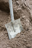 Shovel In Sand. Close up of bricklayers shovel dug into loam sand stock photos