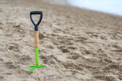 Shovel in the sand of a beach Royalty Free Stock Photo