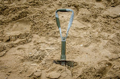 Shovel in the sand on the beach Stock Image